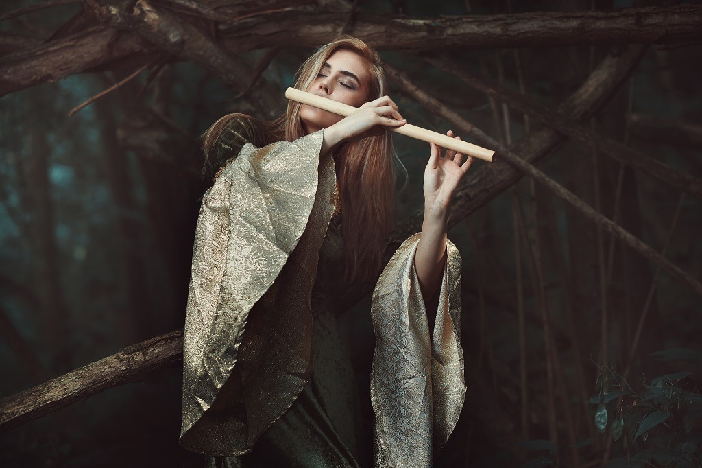 Enchanting lady in brown dress playing flute in an enchanted forest.