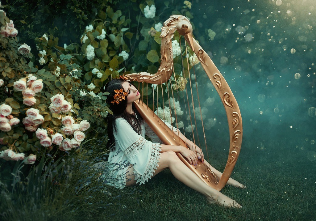 Enchanting forest nymph plays harp in the woods.