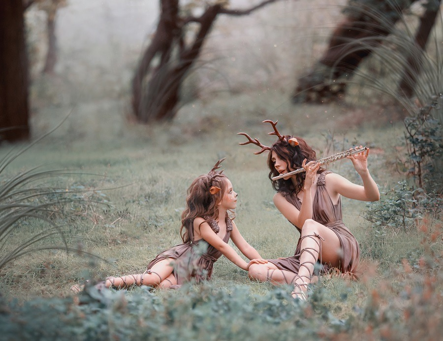 Enchanted creatures, mother playing the flute and child sitting on the grass in the forest.