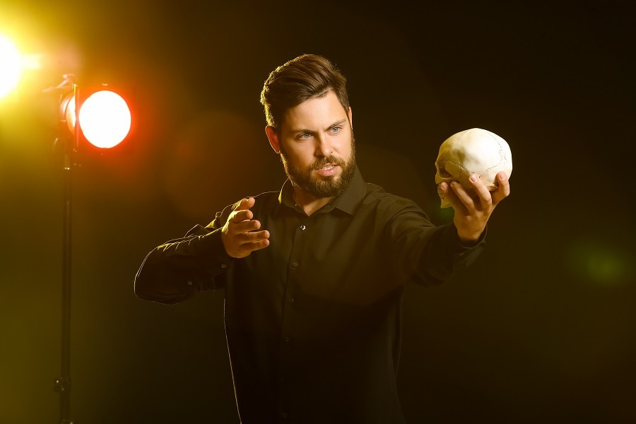 Male actor with human skull on stage.