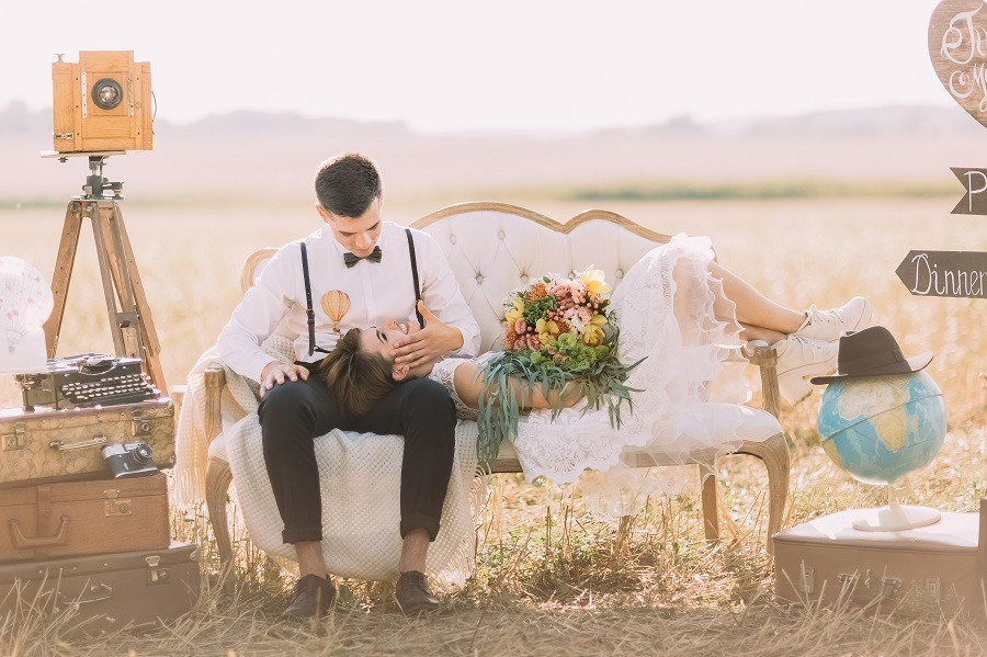 Smiling bride with colourful bouquet is lying on the lap of her vintage dressed groom at a summer field.