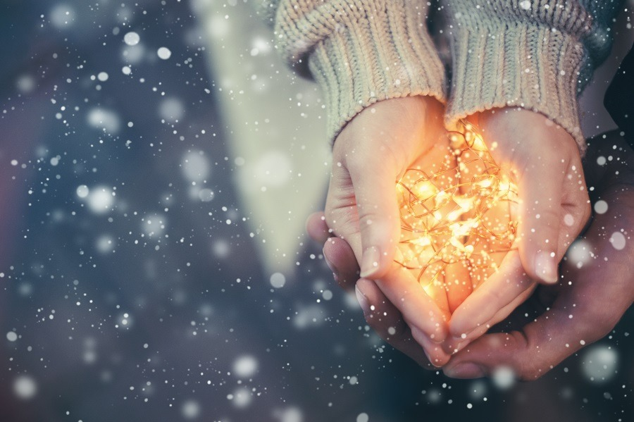 Couple's hands holding warm Christmas lights.