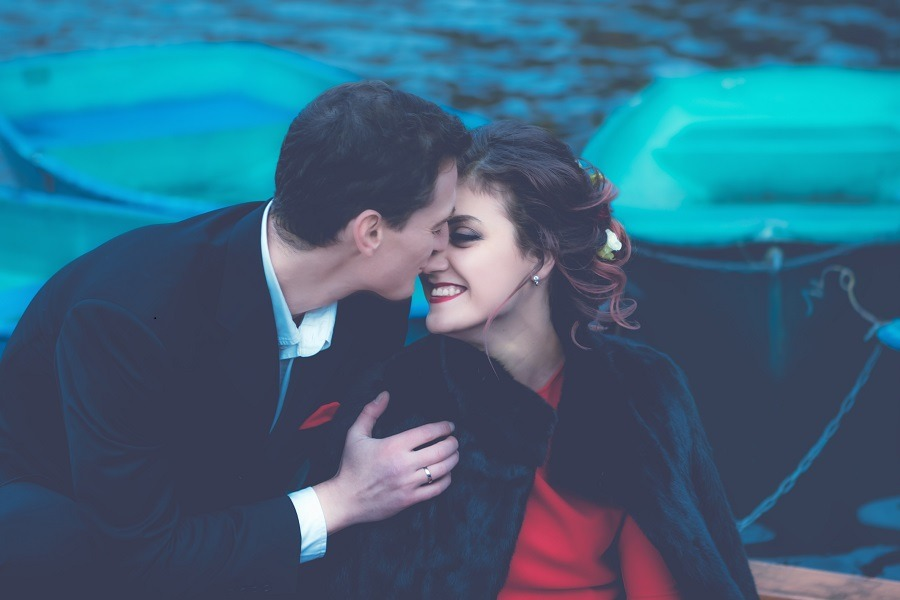 Romantic couple on a boat faces very close.