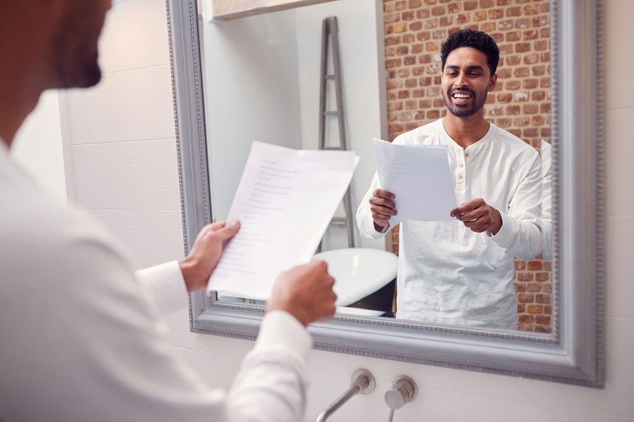 Man at home practicing reading speech in front of the mirror.