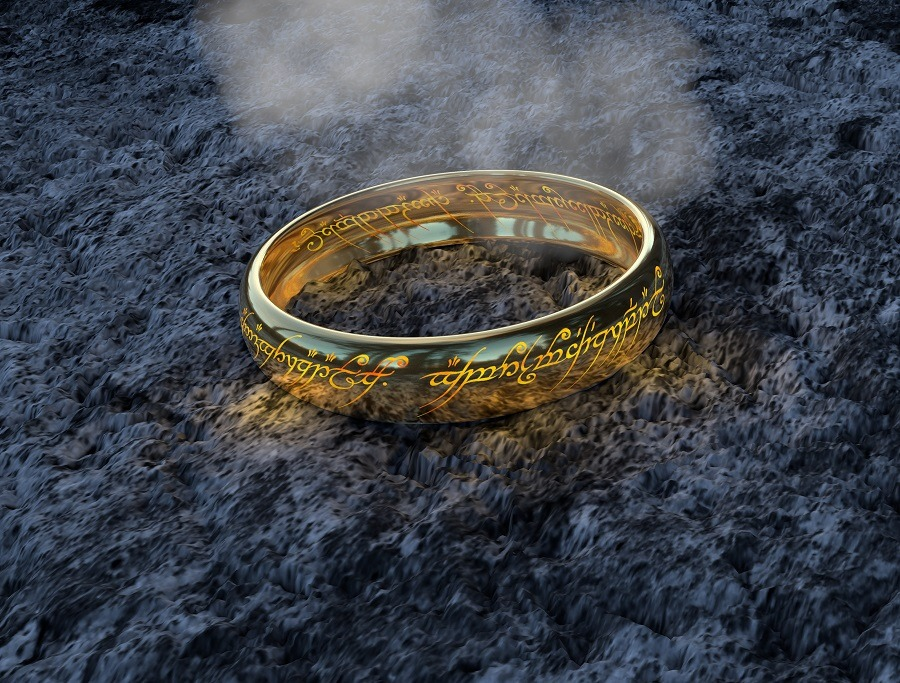 The Lord of the Rings ring on dark gray soil, smoke floating in the backround.