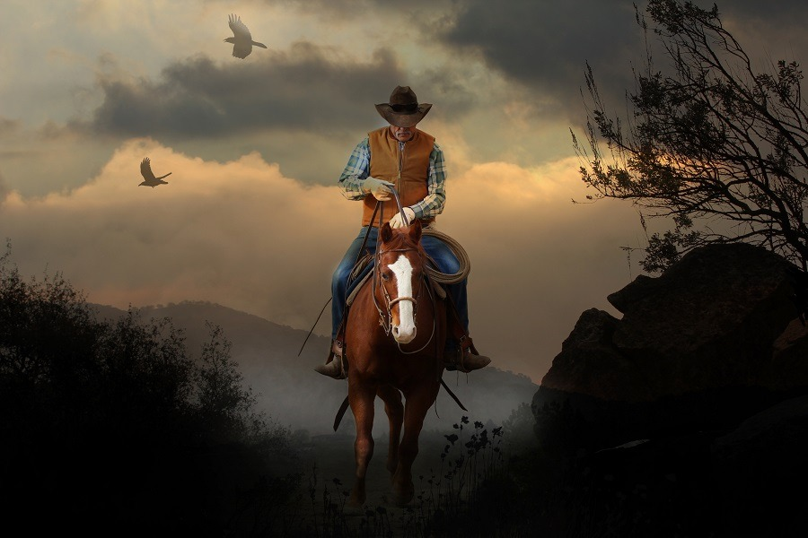 A mountain cowboy rides to the peak of a mountain with a beautiful cloudy sunset.