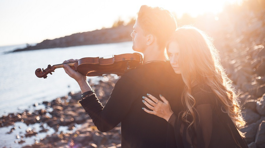 Girl hugging man from back as he plays the violin at seaside.