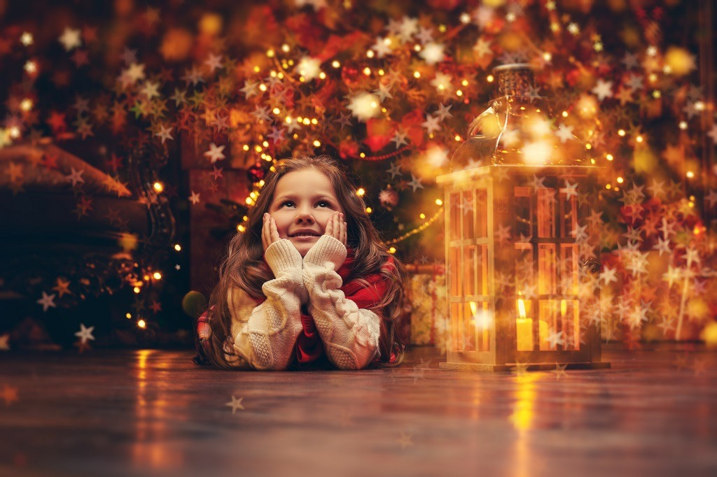 Cheerful little girl lies on the floor in front of Christmas tree with bright lights.