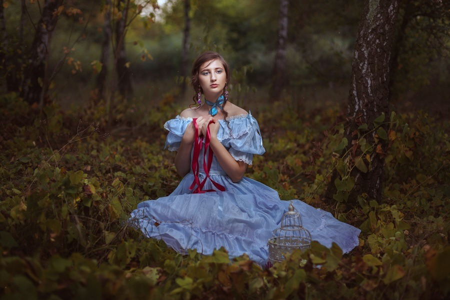 Elegant and pretty lady in blue dress sitting on the grass.