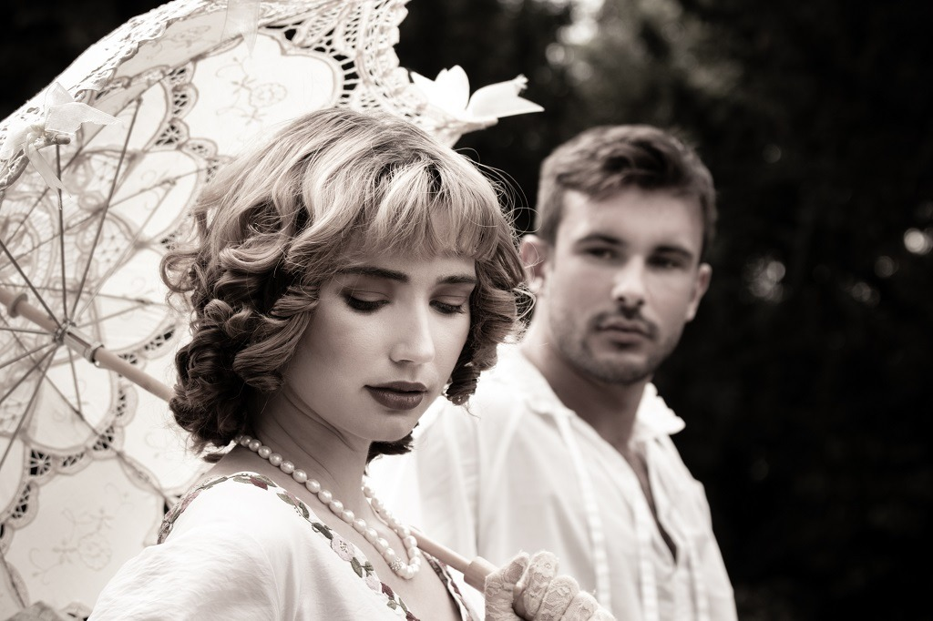 Handsome young couple in vintage clothing with beautiful lady looking down as handsome man looks at her lovingly.