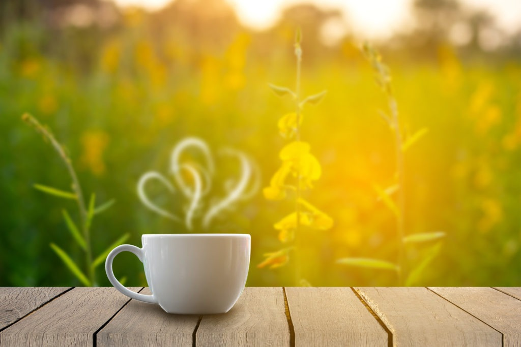Hot coffee cup of love on table blurred flower background
