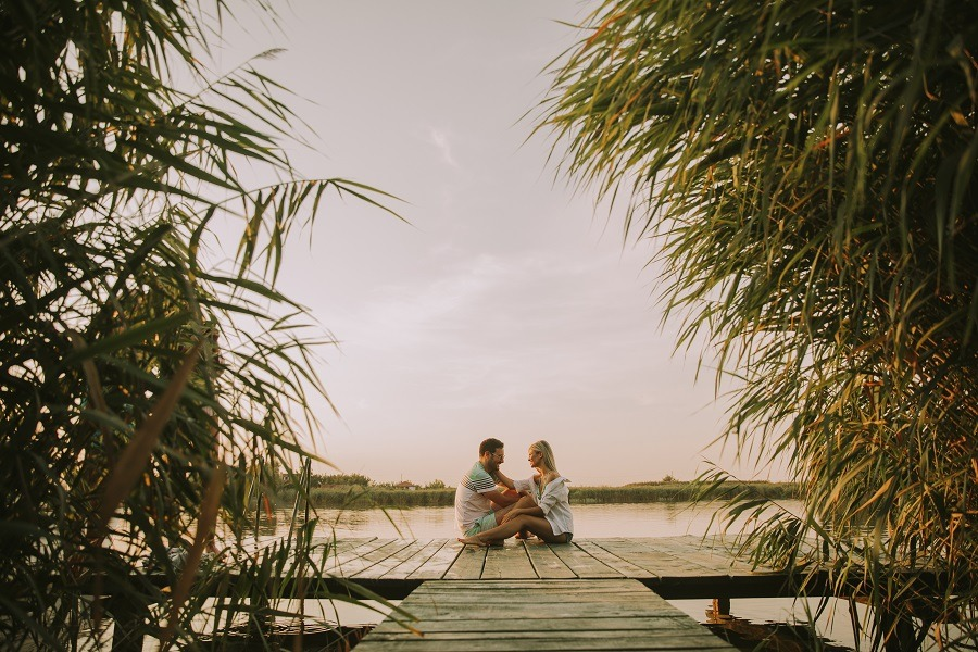 Romantic couple sitting on the wooden pier on the lake.