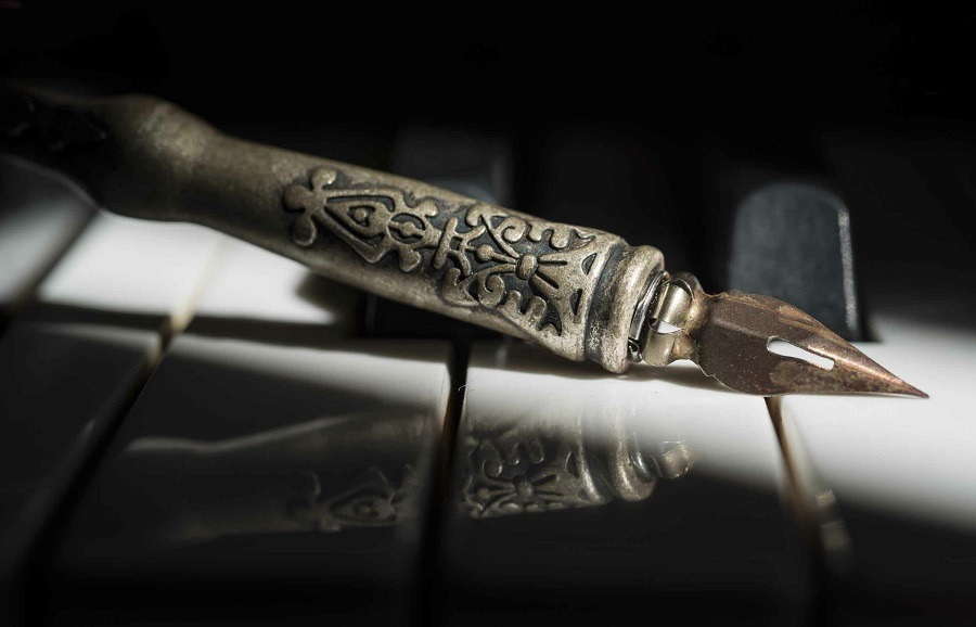 A vintage pen sitting on top of the piano keys.