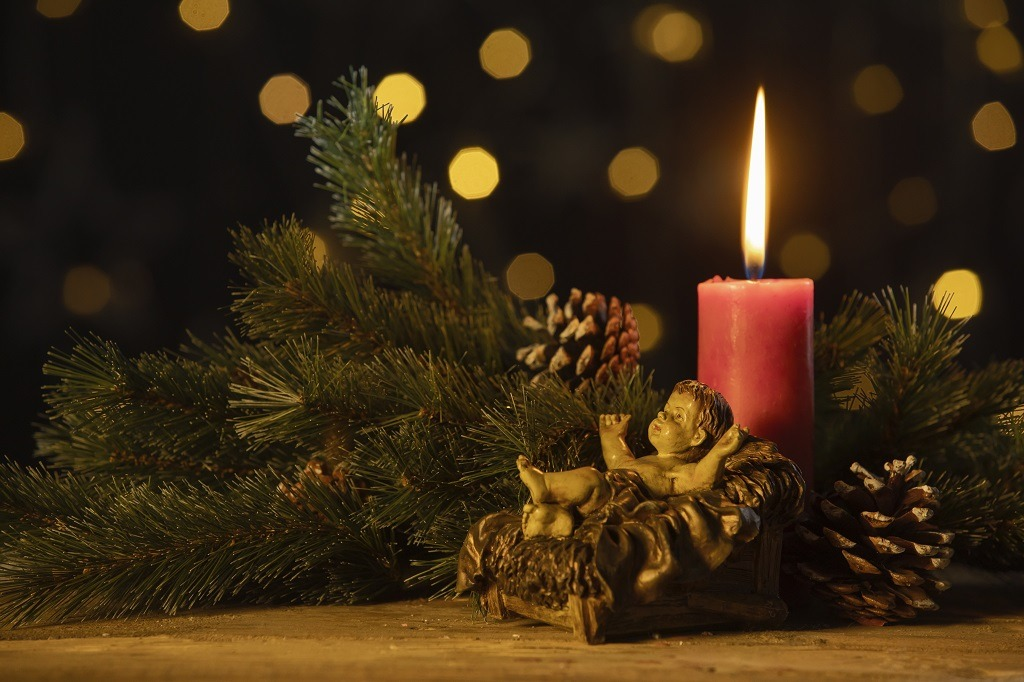 Christmas candle with statuette of baby Jesus.
