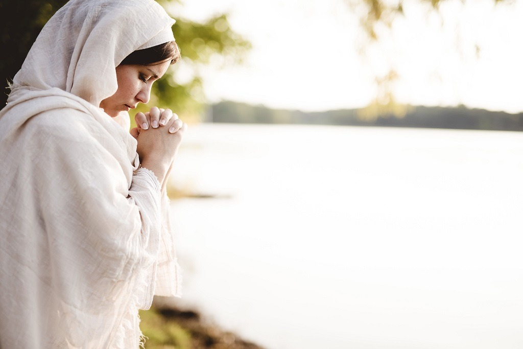 Mary wearing a gown and praying while her eyes are closed.