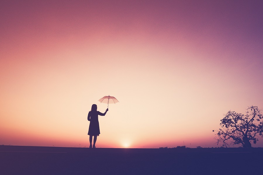 The silhouette of the lonely young woman holding an umbrella on the cliff at the sunset/