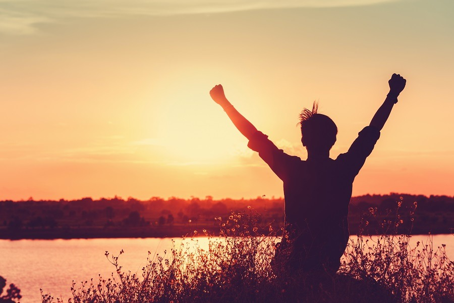Happy young man looking at the sunset arms raised expressing joy and freedom in victory.