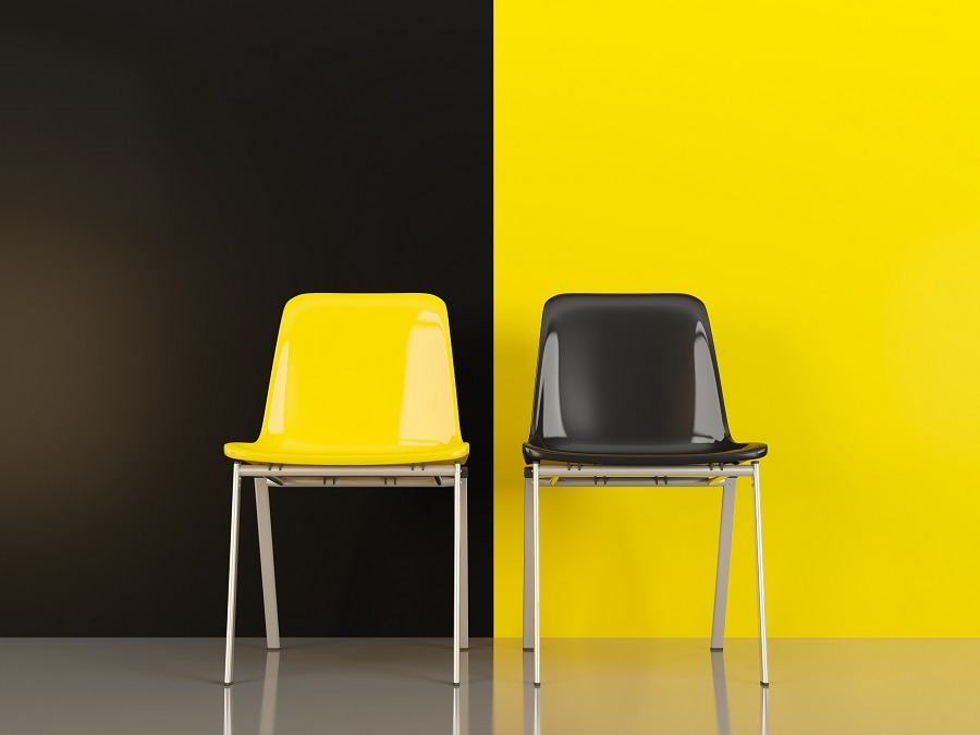 A yellow and a black chair contrasting the black and yellow wall.