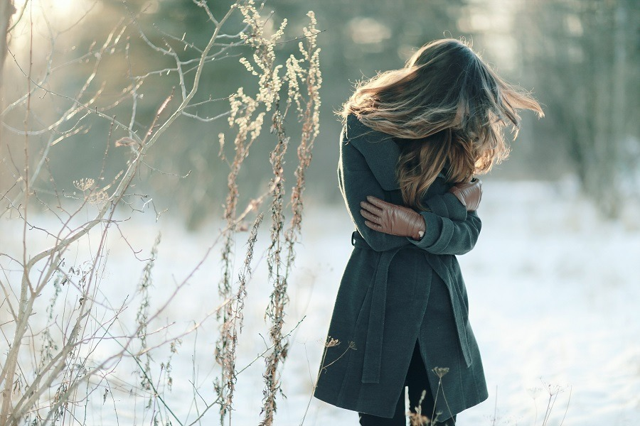 Woman outdoor in winter in emotional pain, hugging herself tightly.