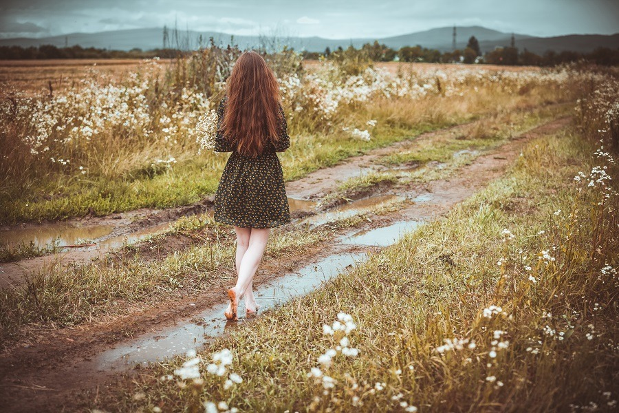 Lonely girl going on rural road with wild flowers in the background.