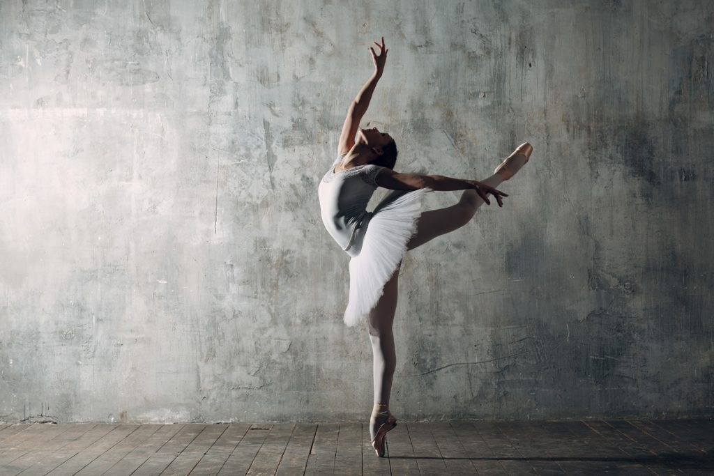 A young female ballerina in perfect arabesque position.