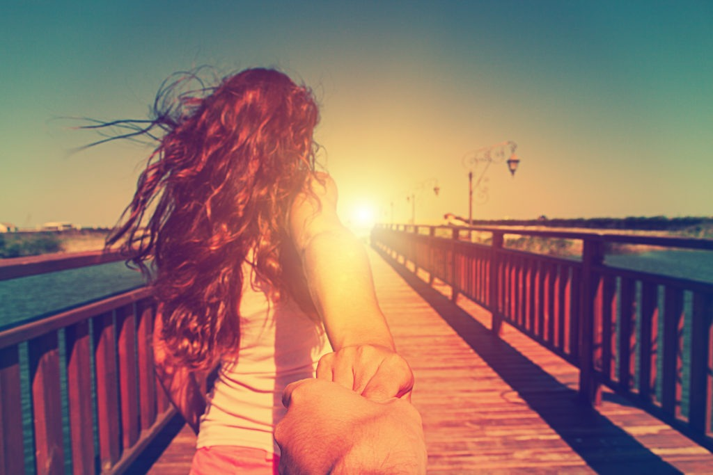 Back view of young girl running toward the sunset on a bridge, holding a man's hand.