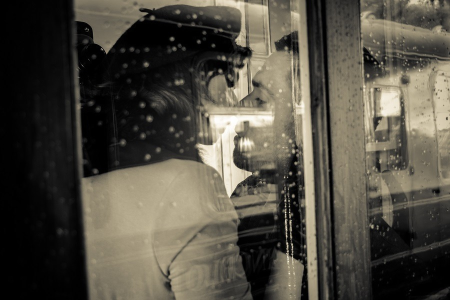 Secret lovers kissing and holding each other passionately in phone booth.