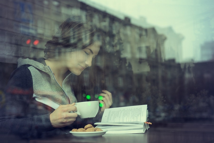 Young woman drinking coffee while reading poetry indoor.