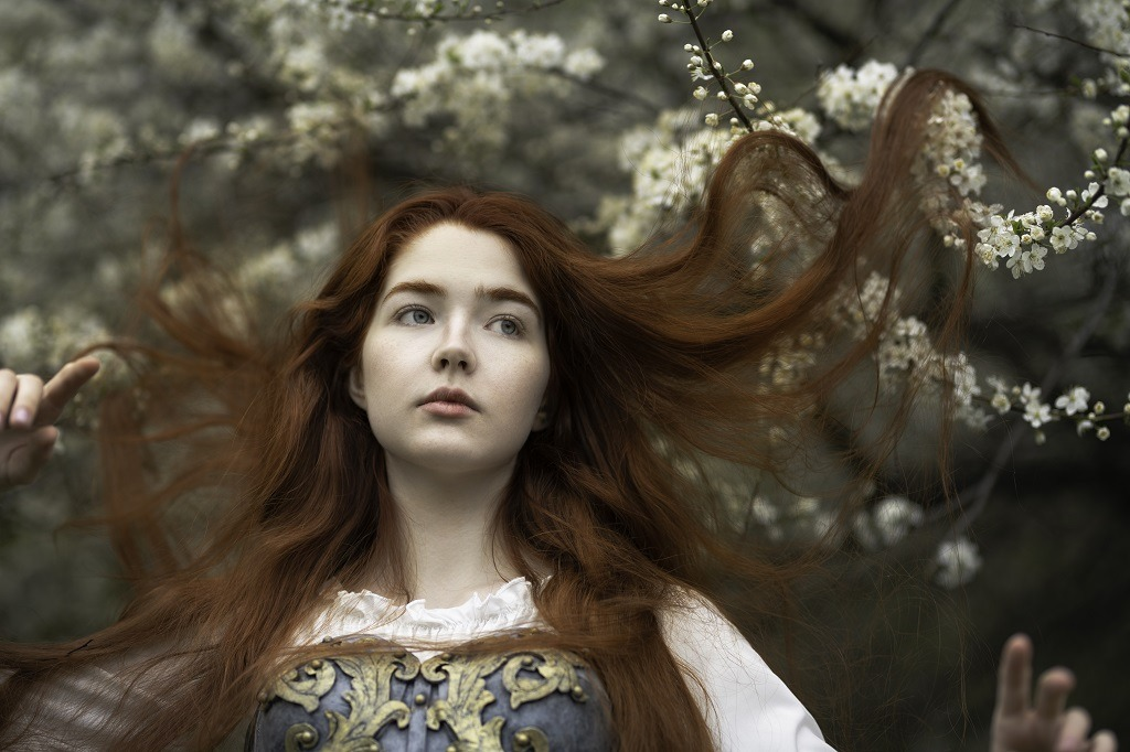 Red-haired girl with hair sprinkled in cherry blossoms.