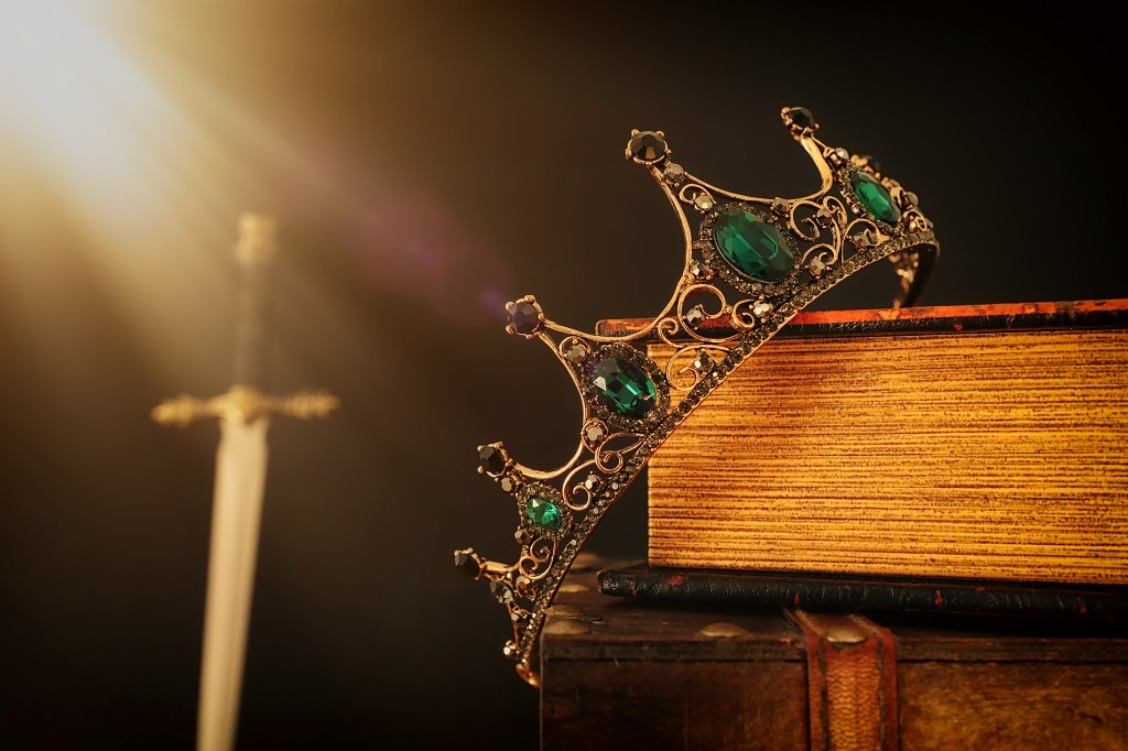 A king's crown over antique book next to a sword.