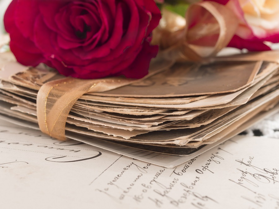Pile of vintage letters with a red stem rose on top.