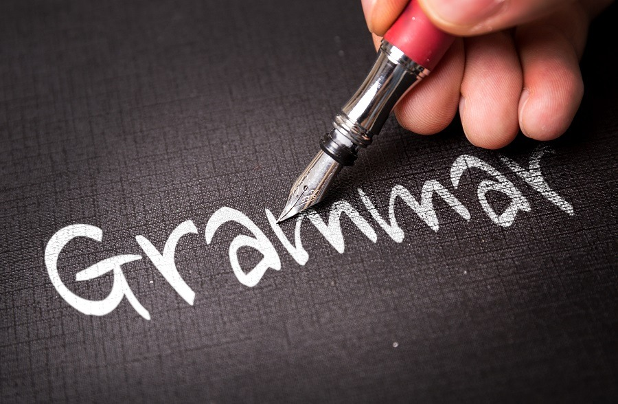 Focus on pen and hand writing the word grammar.