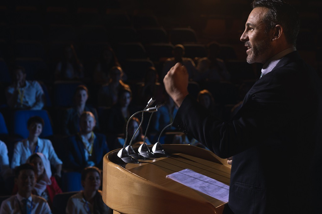 A man standing and giving presentation in the auditorium.