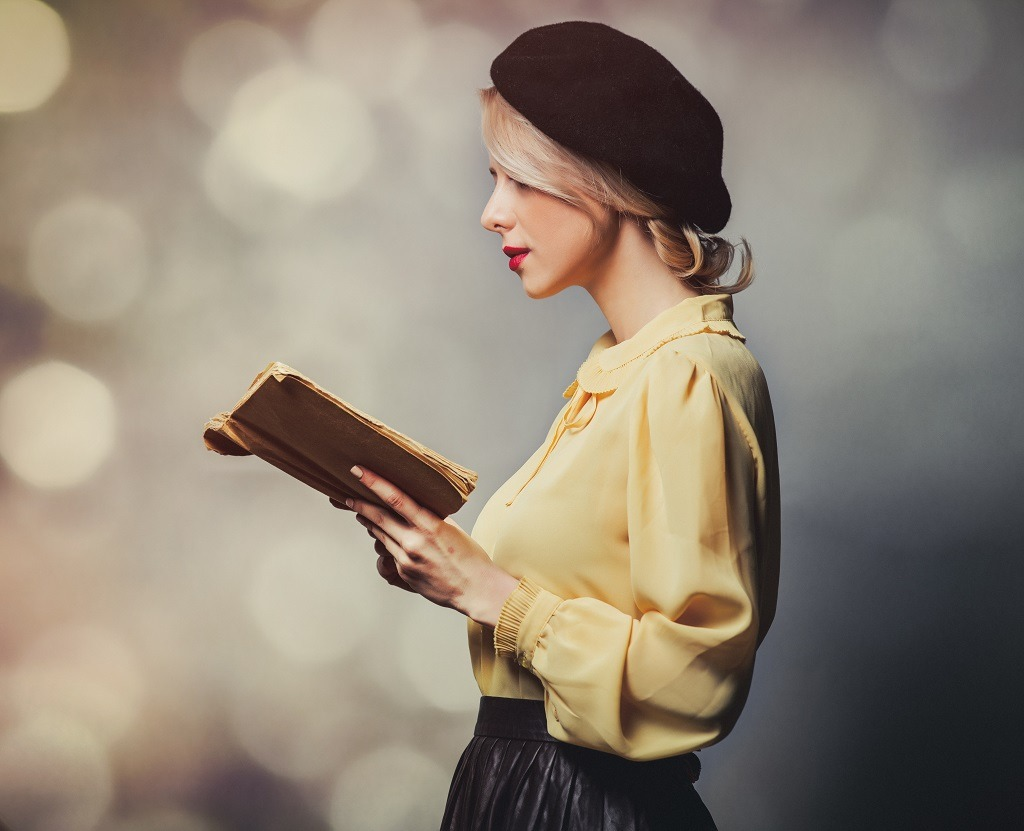 Beautiful girl in vintage clothes with book on gray background.