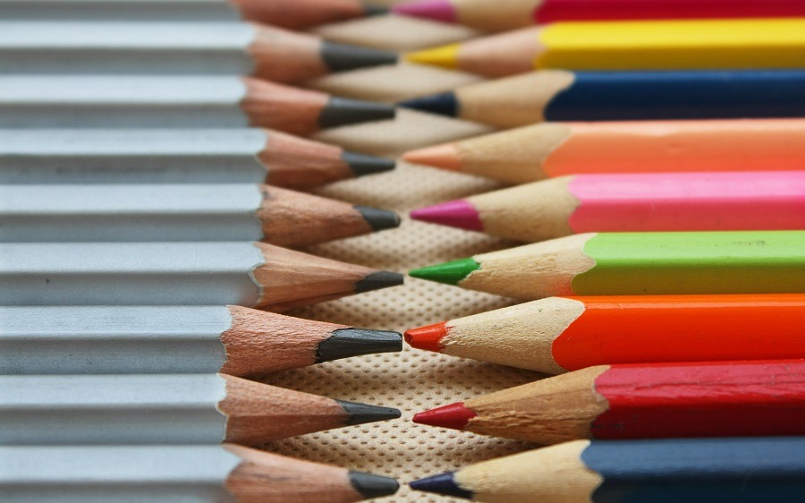 Two different set of color pencils, pointed tips facing each other