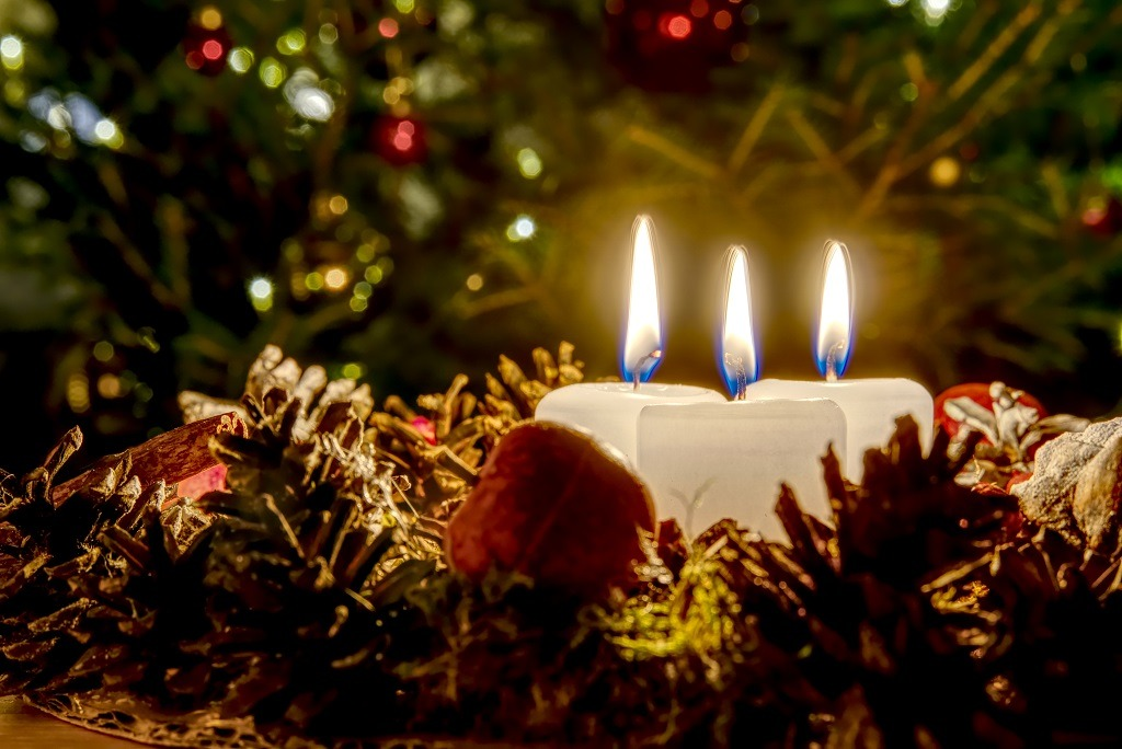 Three burning candles with Christmas pine cones around.
