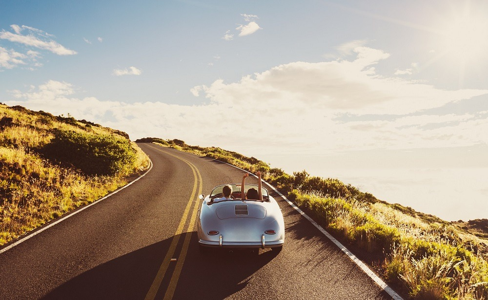 A happy couple driving on a country road in a vintage sports car.