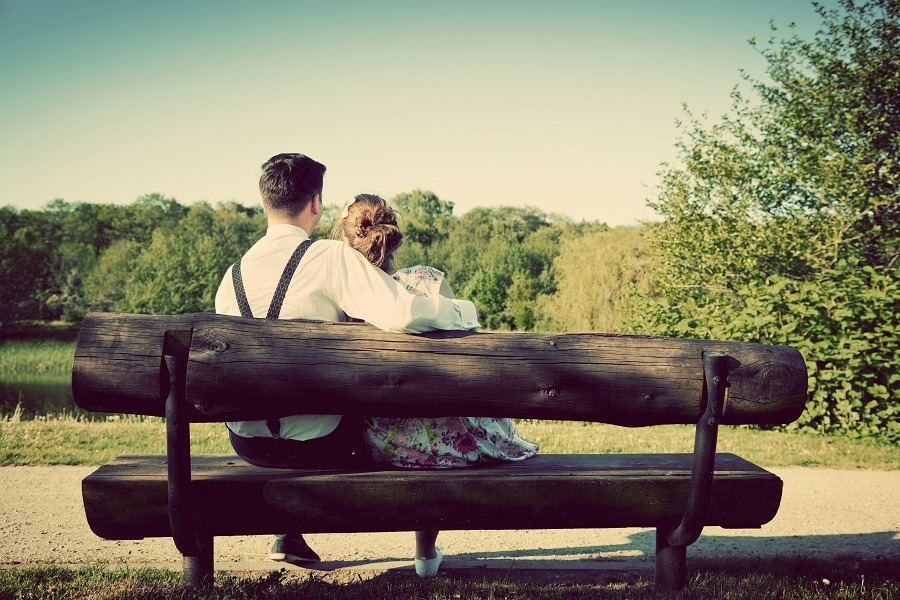 Young vintage couple in love sitting on a wooden bench in the park.