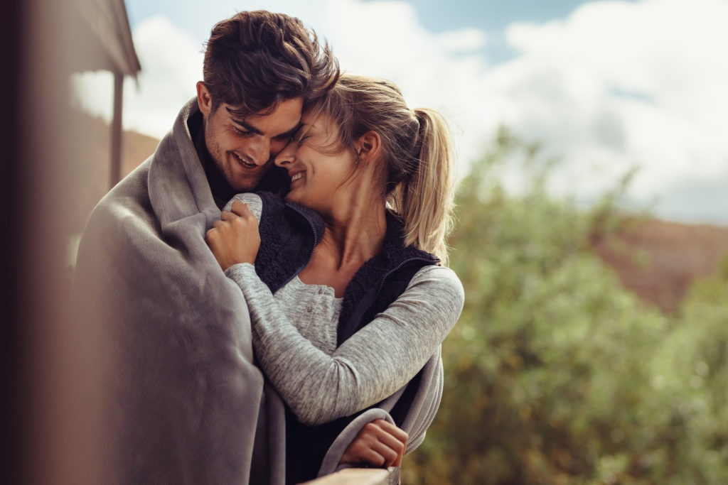 Romantic couple wrapped in blanket outside