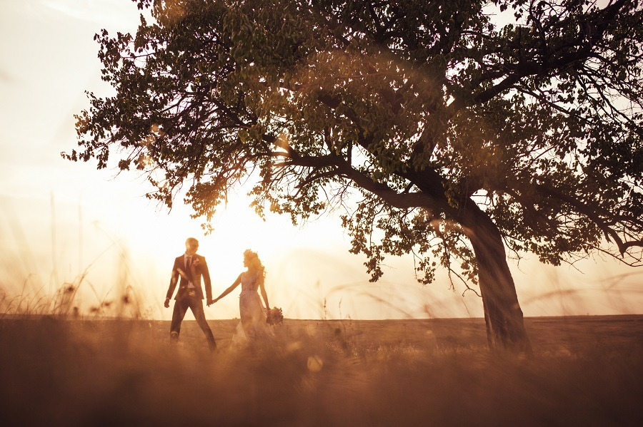 Rustic theme groom and bride going through the field on sunset.