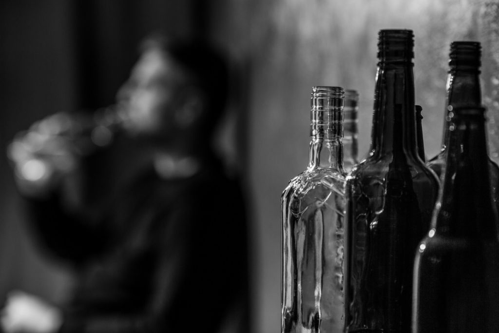 Close-up on alcohol bottles and blurred drunk man in the background.