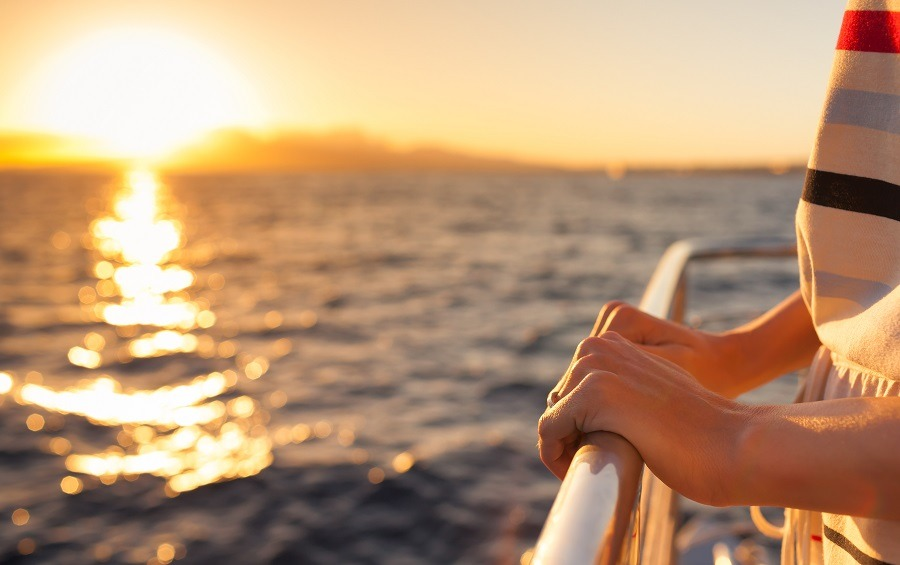Close-up of a woman's hands holding onto a boat railing, sailing into the sunset.