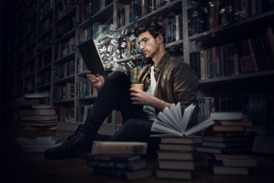 A man reads a book in a library, visualizing images while reading.