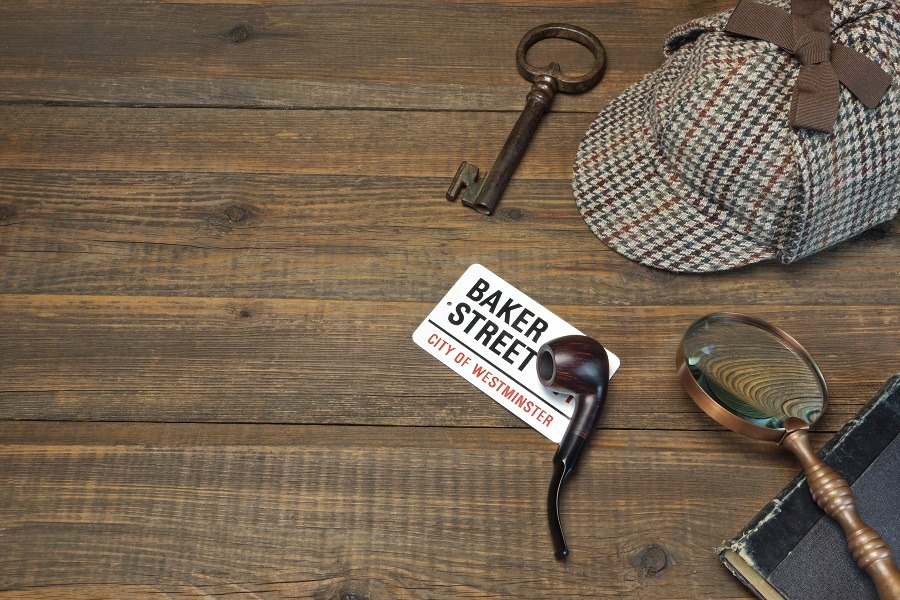 Sherlock Holmes private detective tools on wooden table.