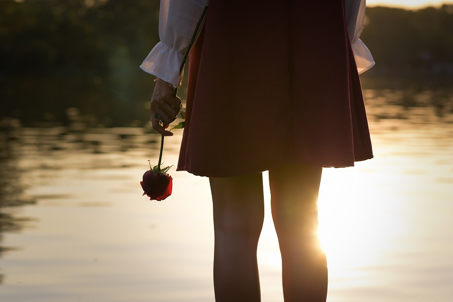 Lonesome woman looking out over the lake with one hand holding a stem rose upside down.