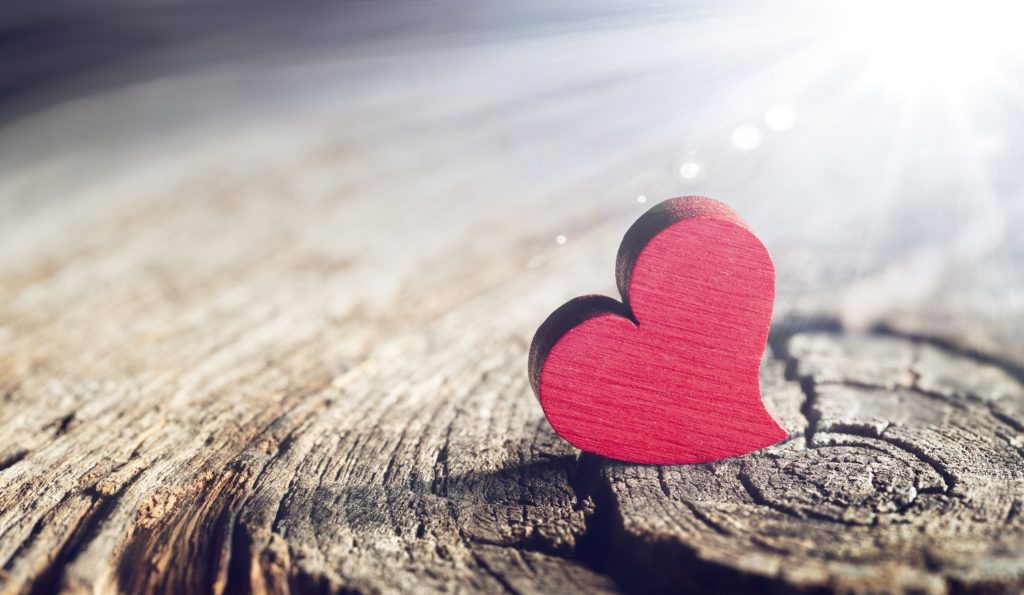 A red-painted wooden heart with sunlight and flare background effect.