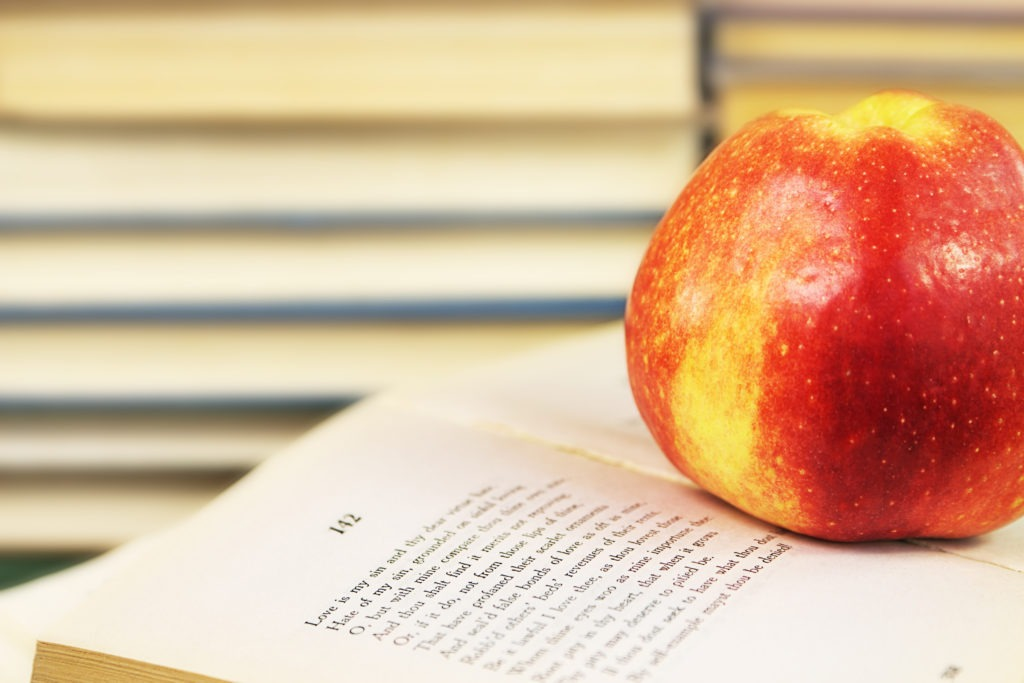 A large red apple on an open book with Shakespeare's sonnets on the background of a shelf with books.