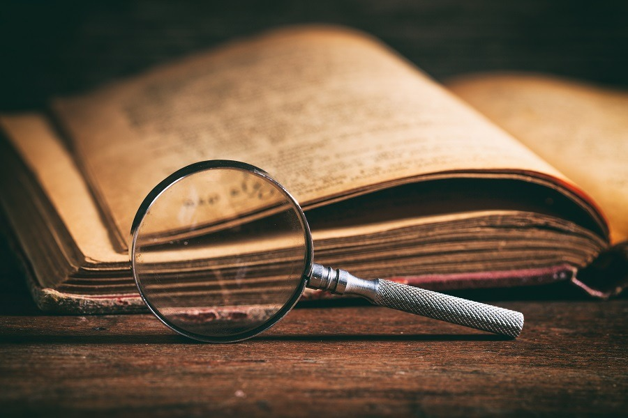 Vintage book and magnifying glass on wooden desk.