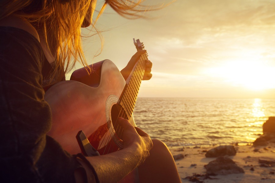 Lonesome beautiful young woman playing guitar on quiet sunset beach.