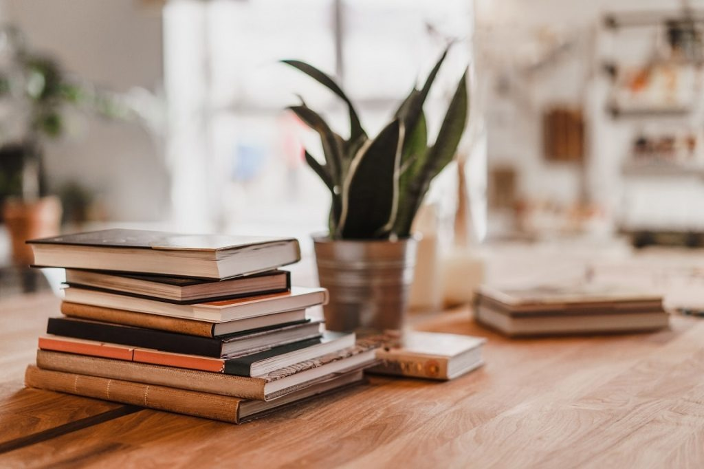 Stack of books on a wooden table in a room.